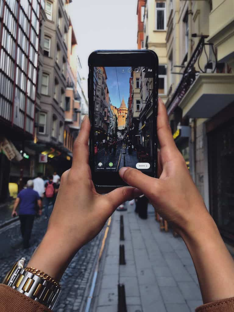 person holding smartphone taking photo of building